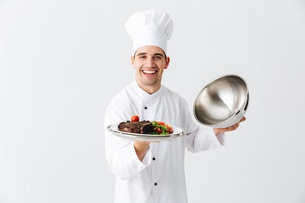 Cuoco unico dell'uomo emozionante che indossa la copertura della cloche di apertura uniforme isolata sopra la parete bianca, mostrando il piatto della carne