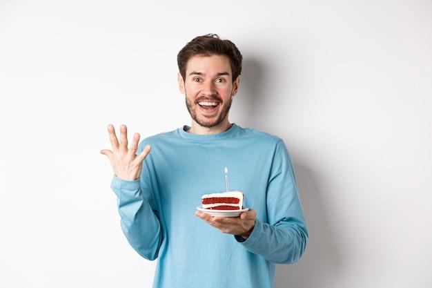 L'uomo eccitato riceve una sorpresa di compleanno, tiene in mano una torta di compleanno e sorride felice, in piedi su uno sfondo bianco, esprimendo un desiderio sulla candela accesa.