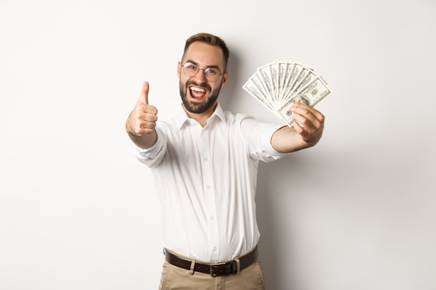 Uomo eccitato che mostra pollice in alto e denaro, guadagnare denaro, in piedi su sfondo bianco