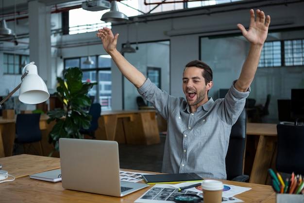 Uomo emozionante che si siede con il computer portatile allo scrittorio