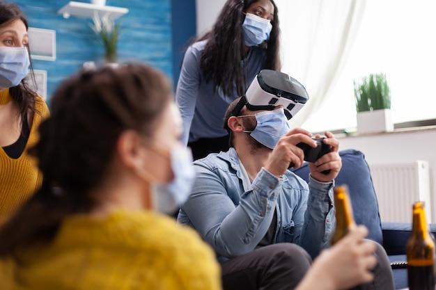 Uomo eccitato che trascorre del tempo con gli amici sperimentando la realtà virtuale giocando con l'auricolare vr che indossa una maschera facciale per prevenire la diffusione del coronavirus in tempo di pandemia sociale.