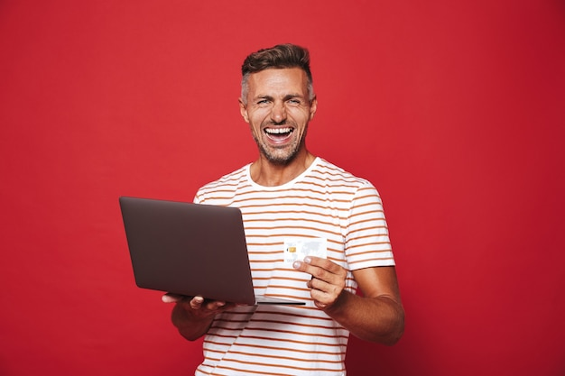 Uomo eccitato in maglietta a righe che sorride mentre tiene in mano una carta di credito e un computer portatile isolato su rosso