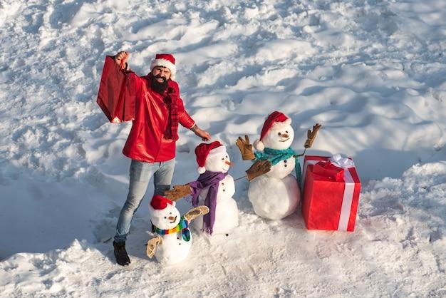 Uomo eccitato con pupazzo di neve divertente in elegante cappello e sciarpa sul campo nevoso. famiglia felice del pupazzo di neve di inverno