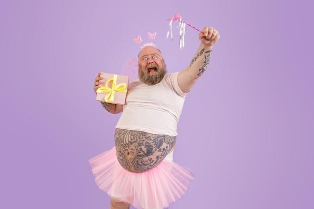 L'uomo eccitato con sovrappeso in costume da fata tiene un bastone magico e presenta su sfondo viola