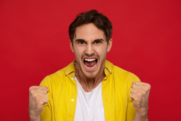 Uomo eccitato in camicia gialla che mostra sì gesto e urla, stringe i pugni nel gesto della vittoria, gode del dolce sapore della vittoria
