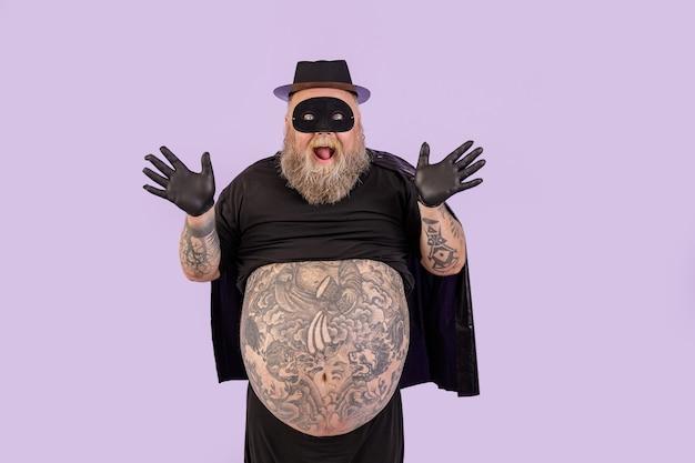 Eccitato uomo maturo con sovrappeso in tuta da eroe alza le mani su sfondo viola