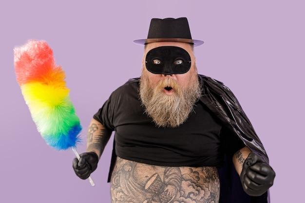 Eccitato uomo maturo con sovrappeso in tuta zorro con pennello per polvere colorato posa in piedi su sfondo viola in studio
