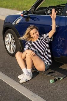 Eccitato donna di mezza età agitando la mano saluto amico seduto su longboard fuori dall'auto in campagna