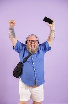 Emozionato uomo grasso di mezza età con cuffie e borsa a tracolla alza le mani e il cellulare con schermo vuoto in posa su sfondo viola in studio