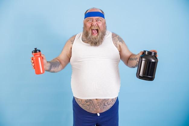 Eccitato uomo grassoccio di mezza età con fascia tiene bottiglie di bevanda e integratore proteico in posa su sfondo azzurro in studio