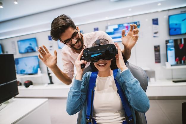 Belle coppie moderne emozionanti che provano camper in negozio di tecnologia.