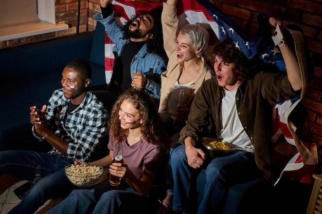 Eccitati amici americani multiculturali appassionati di calcio riuniti a casa in una stanza buia guardando in tv il gioco sportivo si sente euforico in attesa di gol, hobby, spettatori di tornei, concetto di scommesse sportive