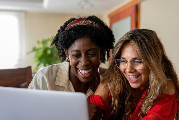 Fidanzate multietniche eccitate che usano insieme il laptop