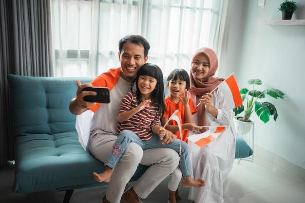 Emozionata famiglia asiatica musulmana che fa selfie e videochiamata usando il telefono a casa mentre tiene in mano la bandiera indonesiana