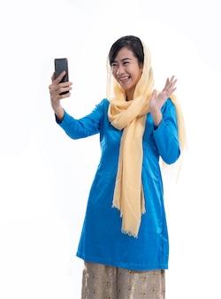 Video chiamata emozionante della donna musulmana facendo uso dello smartphone mobile