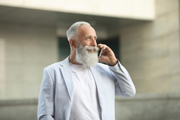 Eccitato uomo anziano in giacca con i capelli bianchi e la barba parlando al telefono