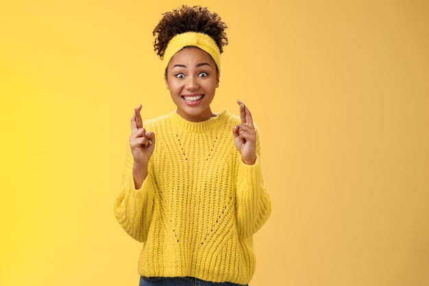 Eccitato ottimista speranzoso giovane timida ragazza afro-americana in maglione giallo sorridente ampiamente entusiasta anticipando buone notizie fortuna bealive incrociare le dita buona fortuna sorridendo si aspettano buone notizie.