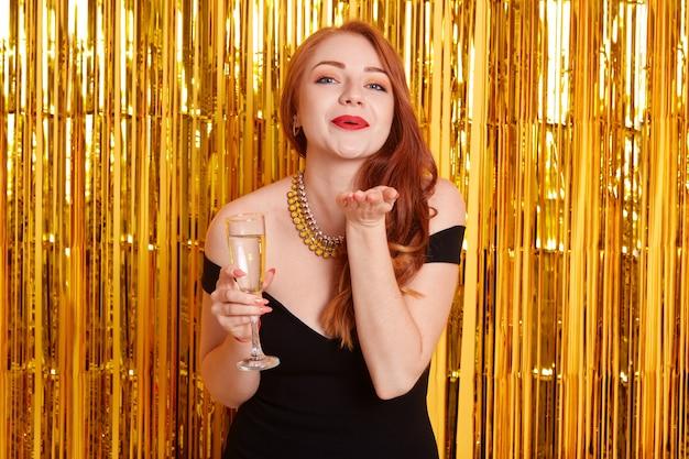Eccitata bella ragazza dai capelli rossi che tiene il bicchiere di vino di champagne frizzante in piedi isolato su sfondo scintilla. modella che manda baci d'aria mentre celebra un evento importante.