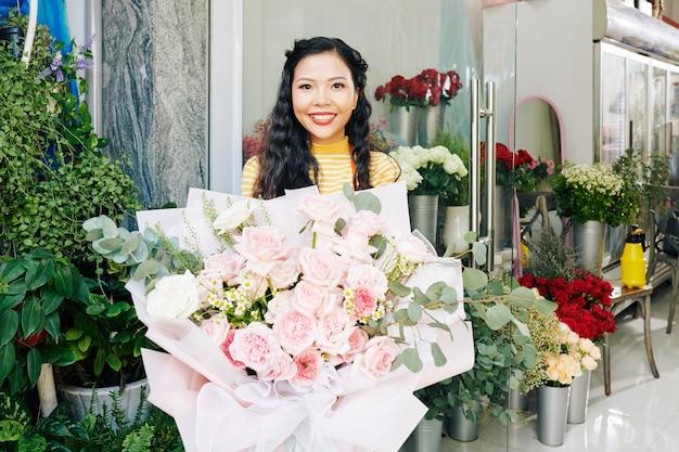 Eccitato piuttosto giovane fiorista vietnamita che mostra un grande bouquet stupendo che ha creato per il cliente