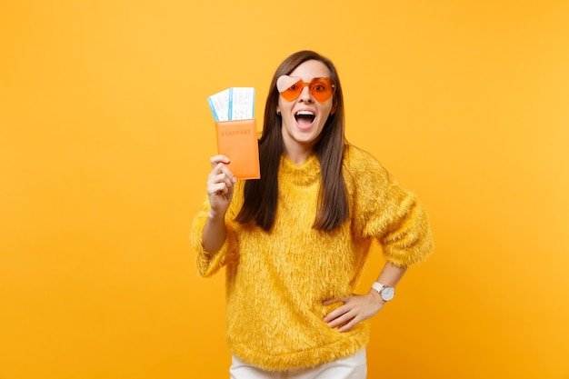 Eccitata bella giovane donna in maglione di pelliccia, occhiali a cuore arancione con passaporto, biglietti per la carta d'imbarco isolati su sfondo giallo brillante. persone sincere emozioni, stile di vita. zona pubblicità.