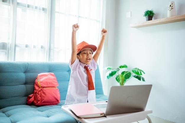 Studentessa della scuola elementare eccitata con l'uniforme alza il braccio durante la lezione online