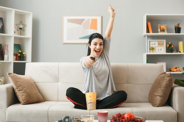 Eccitato alzando la mano giovane ragazza con secchio di popcorn tenendo il telecomando della tv, seduto sul divano dietro il tavolino in soggiorno