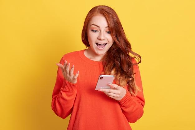 Eccitata donna dai capelli rossi guardando lo schermo del telefono intelligente con l'espressione facciale sorpresa