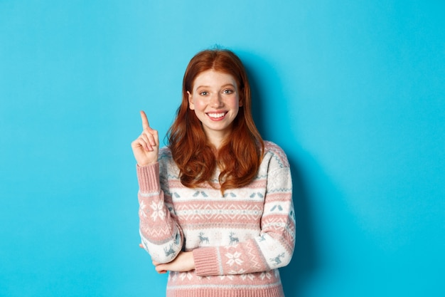 Ragazza adolescente rossa eccitata che ha un'idea, alzando il dito e sorridendo, suggerendo qualcosa, in piedi in maglione su sfondo blu.