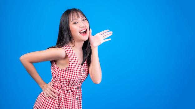 Urla eccitata, bella donna asiatica ragazza carina in abito rosso con frangia stile capelli urla annunciare la buona notizia o promozione, tenendosi per mano vicino al suo viso con la bocca aperta promozione notizie herald