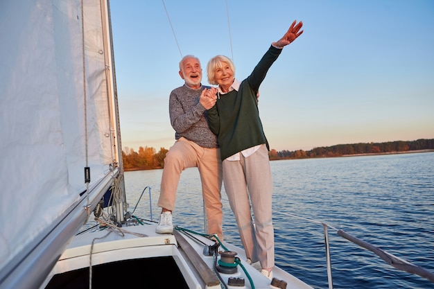 Eccitato coppia anziana che si tiene per mano e sorride mentre si trova sul lato del ponte dello yacht galleggiante