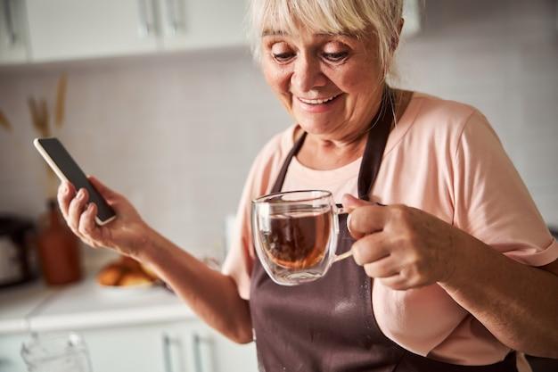 Donna anziana eccitata che mangia tè caldo nella sua cucina