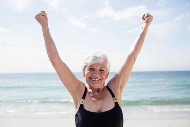 Donna maggiore emozionante che sta sulla spiaggia