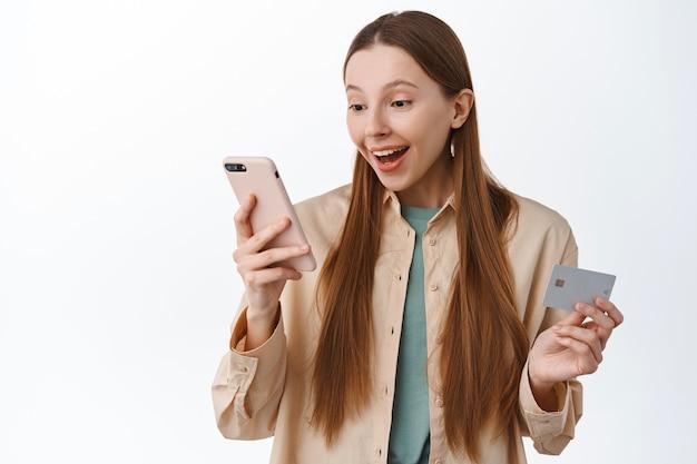 Eccitata ragazza sorridente ordina, acquista online, guarda lo schermo dello smartphone con faccia compiaciuta, tieni la carta di credito, paga in internet, stai in piedi su sfondo bianco.