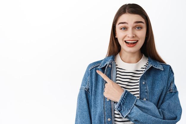 Studentessa sorridente eccitata che indica da parte sul lato sinistro con testo promozionale, mostrando il banner del logo con il dito, sembra interessata, in piedi sul muro bianco