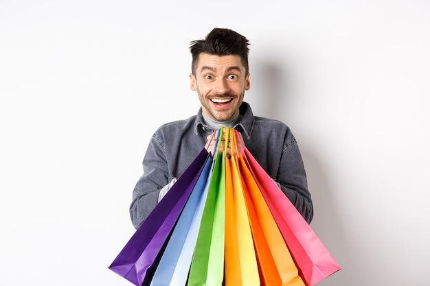 Ragazzo sorridente eccitato che tiene le borse della spesa colorate e si rallegra con sconti in negozio, in piedi su sfondo bianco.