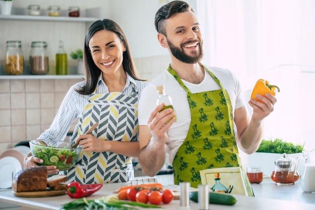 Giovane coppia sorridente eccitata innamorata che prepara un'insalata vegana super sana con molte verdure in cucina e si diverte
