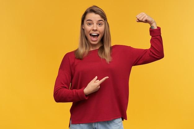 Eccitata ragazza bionda forte e sorridente, splendente di felicità, che mostra i suoi muscoli puntati con il dito indice su di essa, tiene una mano piegata e tiene un pugno chiuso
