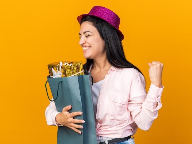 Eccitato con gli occhi chiusi, giovane bella ragazza che indossa un cappello da festa che tiene in mano una borsa regalo che mostra un gesto di sì