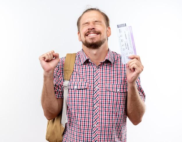 Eccitato con gli occhi chiusi giovane studente che indossa uno zaino con in mano i biglietti che mostrano un gesto di sì isolato sul muro bianco