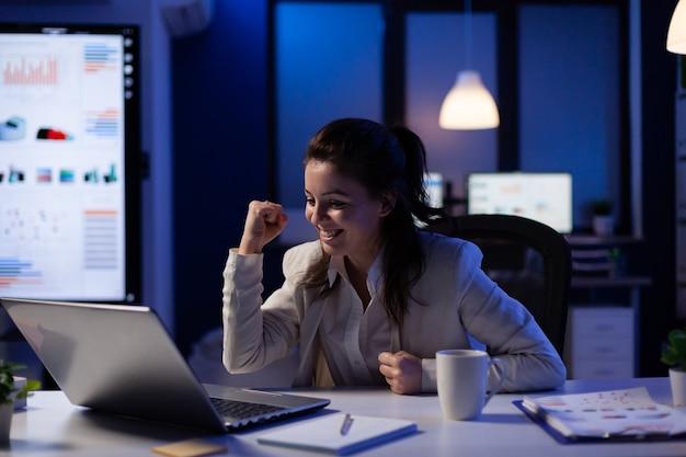 Donna eccitata che controlla il laptop per celebrare il successo della vittoria online leggendo grandi notizie facendo gli straordinari nell'ufficio di avvio