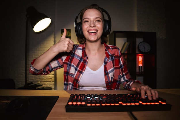 Eccitato giocatore di donna seduta al tavolo, giocando online su un computer in casa, celebrando il successo, mostrando il pollice in alto