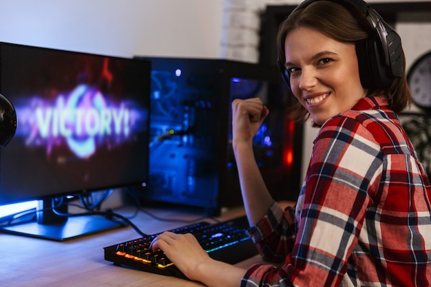 Eccitato giocatore di donna seduta al tavolo, giocando online su un computer in casa, celebrando la vittoria