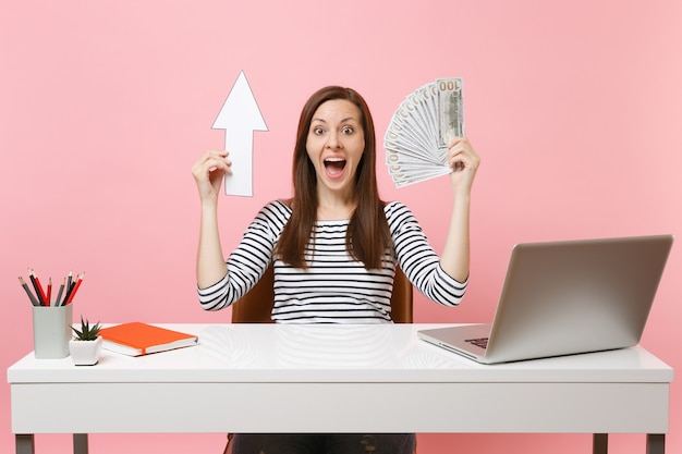 Donna eccitata che tiene in mano un fascio di frecce un sacco di dollari in contanti seduti a lavorare alla scrivania bianca con un computer portatile contemporaneo