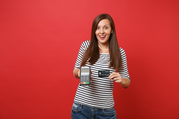 Donna emozionante che tiene il terminale di pagamento bancario moderno wireless per elaborare e acquisire pagamenti con carta di credito, carta nera isolata su sfondo rosso. persone sincere emozioni, stile di vita. mock up copia spazio.