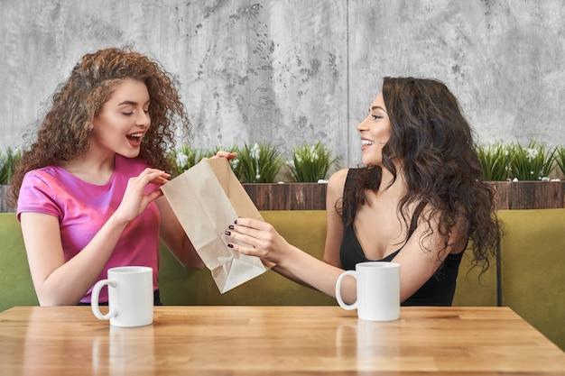Donna emozionante che esamina pacchetto e che prende regalo in caffè