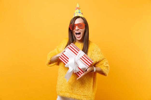 Donna emozionante in occhiali divertenti arancioni, cappello di compleanno che tiene scatola rossa con regalo presente celebrando e godendo la vacanza isolata su sfondo giallo brillante. persone sincere emozioni, concetto di stile di vita.