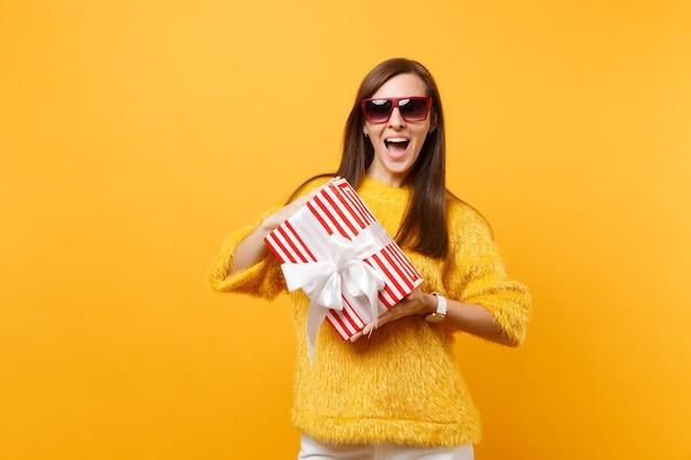 Donna emozionante in occhiali rossi che tengono scatola rossa con regalo presente celebrando, godendo la vacanza isolata su sfondo giallo brillante. persone sincere emozioni, concetto di stile di vita. zona pubblicità.