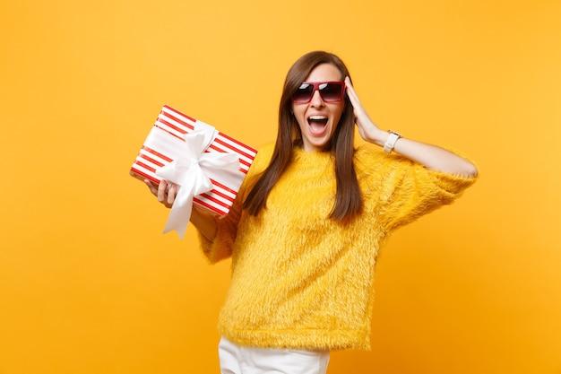 Donna eccitata in occhiali rossi che tiene la mano vicino al viso, tiene in mano una scatola rossa con un regalo, presente godendosi le vacanze isolate su sfondo giallo brillante. persone sincere emozioni, stile di vita. zona pubblicità.