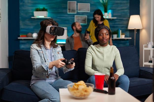 Donna eccitata che trascorre del tempo con amici di razza mista che sperimentano la realtà virtuale giocando con l'auricolare vr durante la competizione di gioco. gruppo multietnico che esce insieme divertendosi.