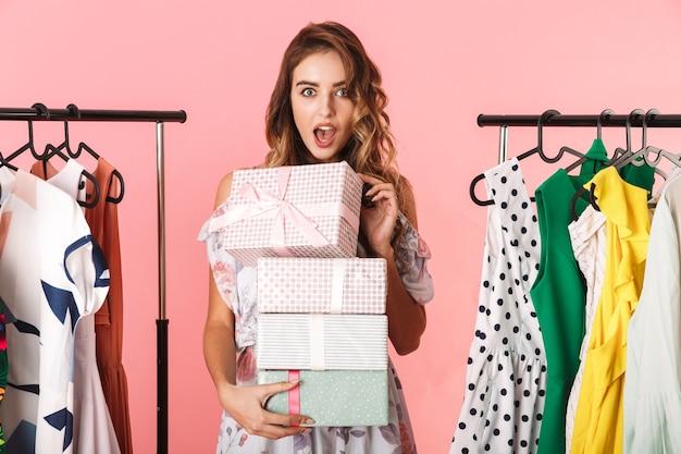 Donna eccitata che indossa un abito in piedi in negozio vicino a stendibiancheria con scatole presenti isolato sul rosa
